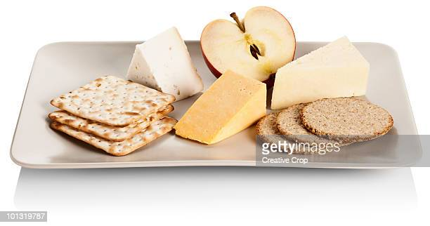 Variety of cheeses on a plate with apple