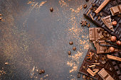 Variety of chocolate bars with spices on an old rusty metal background.Top view.