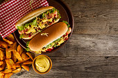 Variety of classic traditional american tasty junk unhealthy food on wooden background with copy space. Hot Dogs and Chips.