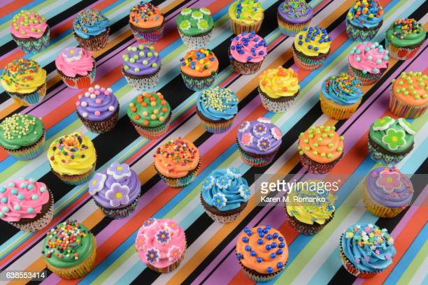 Variety of Cupcakes on a Colorful Striped Background