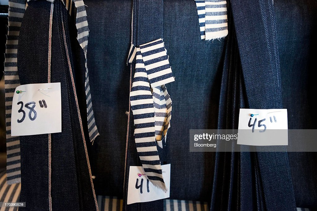 A variety of different sized denim jeans sit unfinished on a rack at Detroit Denim, in Detroit, Michigan, U.S., on Wednesday, June 12, 2013. The Commerce Department is scheduled to release monthly business inventories data on June 13. Photographer: Ty Wright/Bloomberg via Getty Images