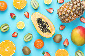 Variety of Different Tropical Seasonal Summer Fruits. Papaya Mango Tangerines Citrus Oranges Pineapple Lemons Strawberries Kiwi Scattered on Blue Background. Healthy Lifestyle Diet Vitamins. Flat Lay