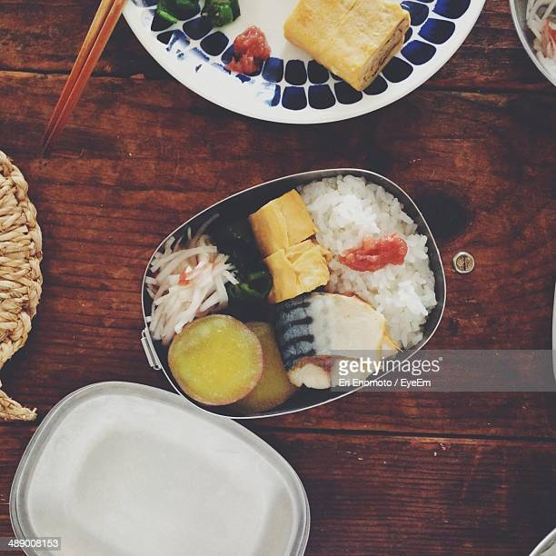 Variety of food in lunch box on wooden table