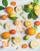 Variety of fresh citrus fruits for making juice or smoothie over light grey marble table background, top view, vertical composition. Healthy eating, vitamin, detox, diet food, clean eating concept