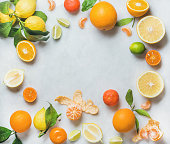 Variety of fresh citrus fruits for making juice or smoothie over light grey marble table background, top view, copy space. Healthy eating, vitamin, detox, diet food, clean eating concept