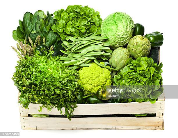 Variety of green vegetables sitting in a wooden box
