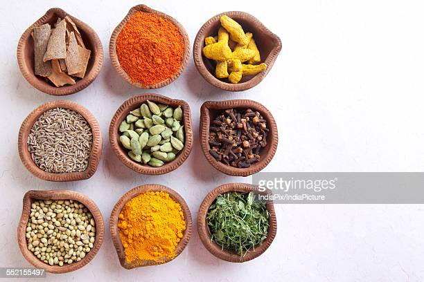 Variety of Indian spices in diyas over white background