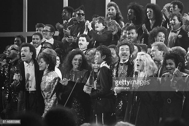 A variety of music and movie stars sing 'We Are The World' a song written to benefit famine victims in Ethiopia Across the front row stands Stevie...