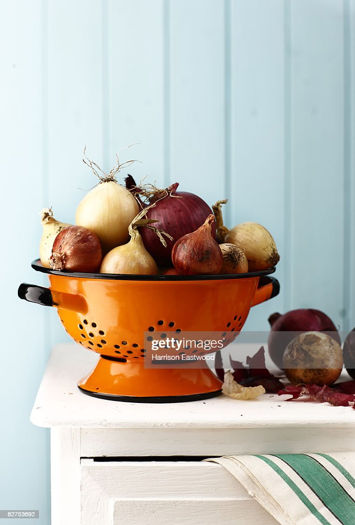 Variety of onions in colander on sideboard : Stock Photo