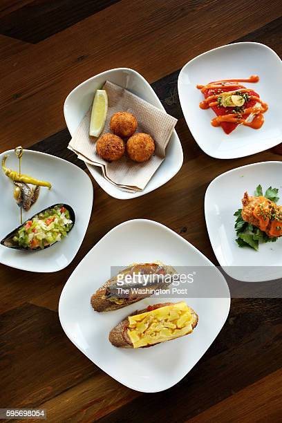 Gilda with Marinated Mussels Shrimp Croquettes CauliflowerStuffed Piquillo Cod Fitters and Escalivada Montadito plated with Tortilla de Patatas...
