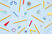 Variety of school supplies on the blue background. Back to school concept. Flatly, directly above.