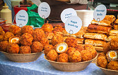 A variety of scotch eggs and other savoury pastry snacks on display at Broadway market, a street market in Hackney, East London