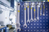Variety of spanners hanging from workstation rack in factory