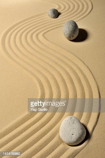 A variety of stones and wave pattern in the sand p : Stock Photo