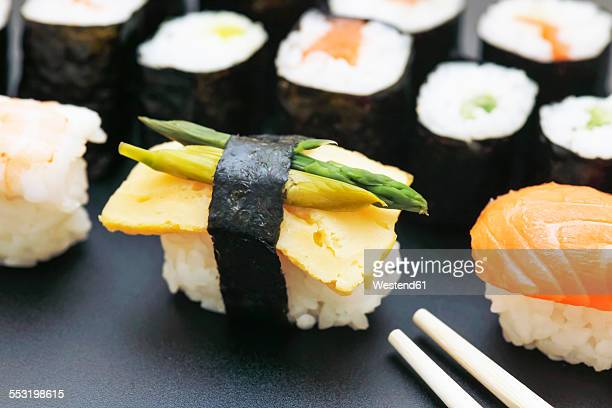 Variety of sushi with green asparagus on plate