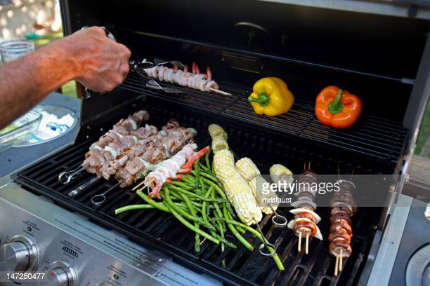 Variety of vegetables and meat kabobs on an open grill