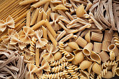 Variety of types and shapes of wholemeal pasta. Dry integral pasta background