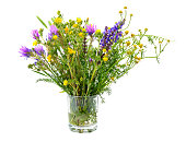 Variety of wild flowers in a glass isolated on white background.