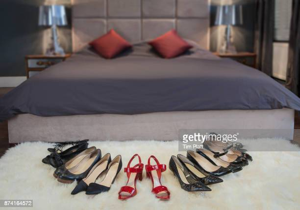 Variety of women's shoes arranged on a bedroom rug