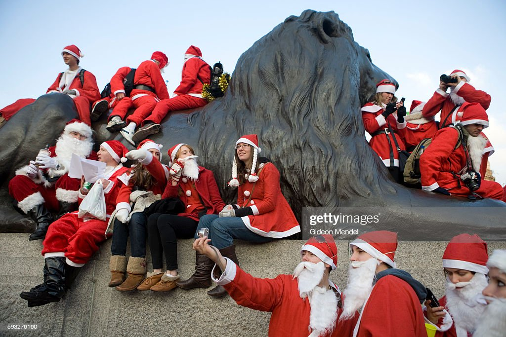 Various bawdy Santas occupy a lion at Trafalgar Square many of them taking photographs during the London SantaCon event SantaCon is a mass gathering...