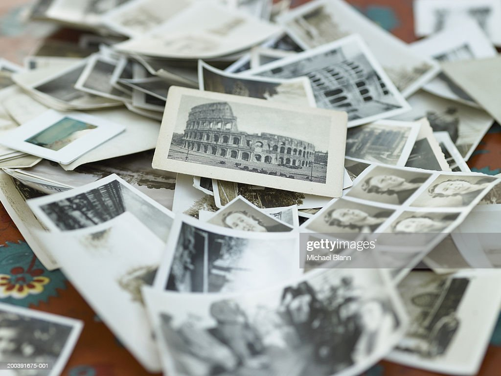 Various black and white photographs in pile on table : Bildbanksbilder