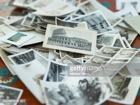 Various black and white photographs in pile on table : Foto de stock