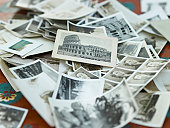 Various black and white photographs in pile on table