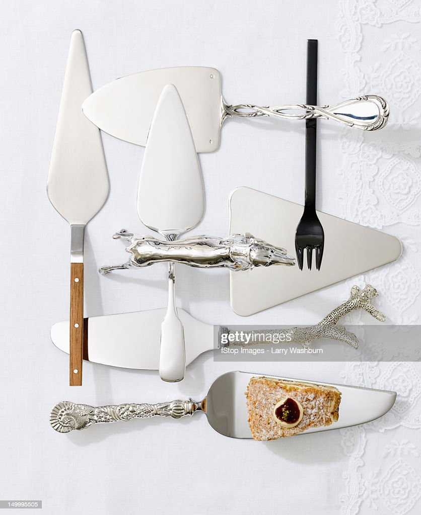 Various cake servers and a slice of cake