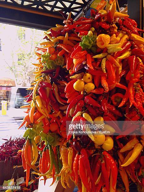 Various Chili Peppers Hanging At Market