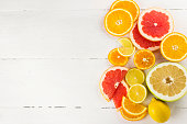 Various citrus on white wooden background