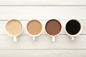 Different cups of coffee on white wooden table, top view. Gradient from light americano with milk to strong black espresso, copy space