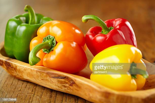 Various colorful bell peppers in wooden basket