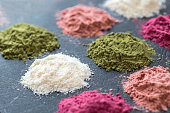 Various colorful superfood powders on dark background. Healthy food supplements, detoxing concept