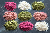 Various colorful superfood powders on dark background. Healthy food supplements, detox concept. Top view