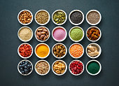 Various colorful superfoods as acai powder, turmeric, matcha green tea, spirulina, quinoa, pumpkin seeds, blueberry, dried goji berries, cape gooseberries, raw cocoa, hemp seeds and other in bowls on