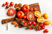 various colorful tomatoes on wooden cutting board, top view