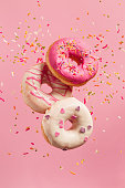 Various decorated doughnuts in motion falling on pink background. Sweet and colourful doughnuts falling or flying in motion.