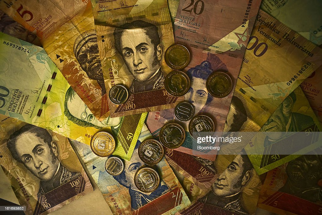 Various denominations of bolivar coins and notes are arranged for a photograph in Caracas, Venezuela, on Wednesday, Feb. 13, 2013. Venezuelan President Hugo Chavez, who hasn't been seen or heard from publicly since arriving in Havana on Dec. 10 for cancer surgery, ordered his government to weaken the exchange rate by 32 percent to 6.3 bolivars per dollar starting on Feb. 13. Photographer: Meridith Kohut/Bloomberg via Getty Images