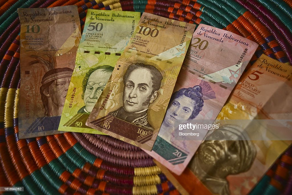 Various denominations of bolivar notes are arranged for a photograph in Caracas, Venezuela, on Wednesday, Feb. 13, 2013. Venezuelan President Hugo Chavez, who hasn't been seen or heard from publicly since arriving in Havana on Dec. 10 for cancer surgery, ordered his government to weaken the exchange rate by 32 percent to 6.3 bolivars per dollar starting on Feb. 13. Photographer: Meridith Kohut/Bloomberg via Getty Images