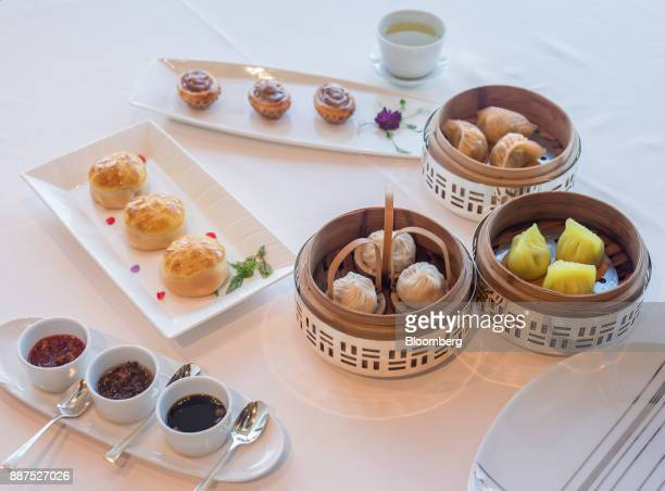 Various dim sum dishes including baked barbecued pork buns with pine nuts clockwise from left baked whole abalone puff with diced chicken steamed...