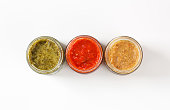 overhead view of assorted dipping sauces or pesto sauces in jars