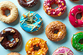 Various colorful donuts on blue background, top view