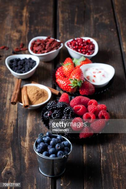 Various dried and fresh fruits and bowl of cinnamon powder with cinnamon sticks on wood