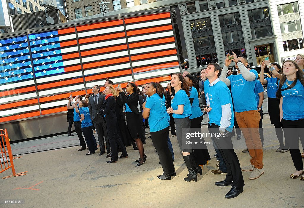 Various executives and Viacommunity Day Volunteers look at the NASDAQ Stock Market banner during the opening bell in honor of Viacommunity Day at the NASDAQ MarketSite on April 22, 2013 in New York City.