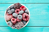 Frozen berries bowl on blue background