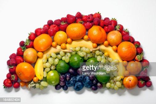 Various fruits arranged into the shape of a rainbow