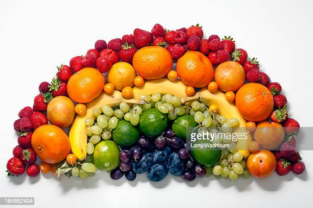 Various fruits arranged into the shape of a rainbow