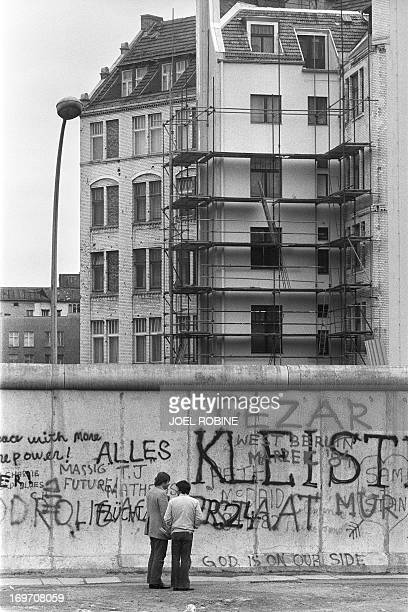 Various graffiti are painted on the Berlin Wall on the West Berlin side on April 29 as two men look on The Berlin wall built by the East German...