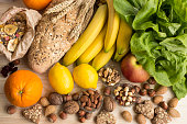 Various Healthy Food, Tropical Fruits, Nuts, Muesli, Whole Wheat Bread and Biscuits, Lettuce, Apple.