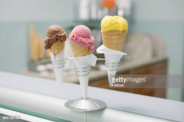 Various ice cream cones in spiral holder on counter at store
